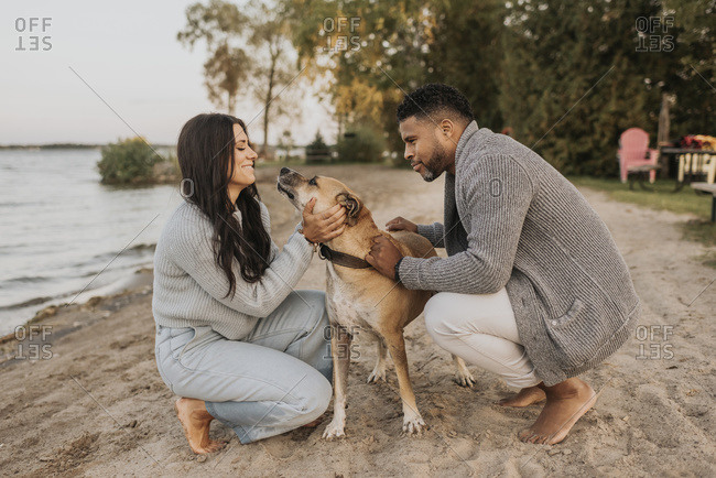 Couple playing with dog while crouching on sidewalk by lake during sunset
