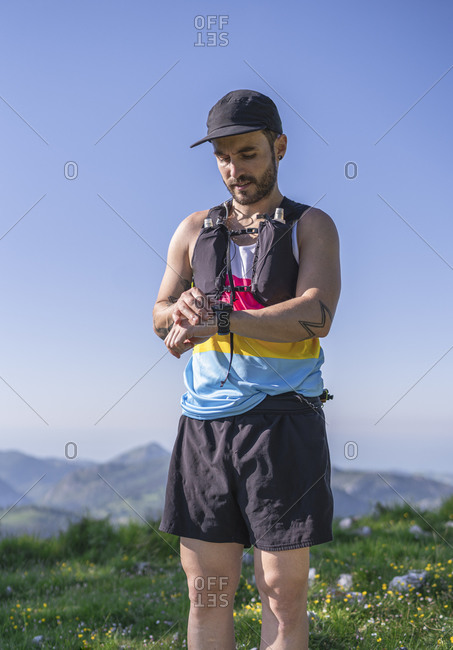 Mid adult man wearing cap and bottle strap checking time on watch while standing on mountain