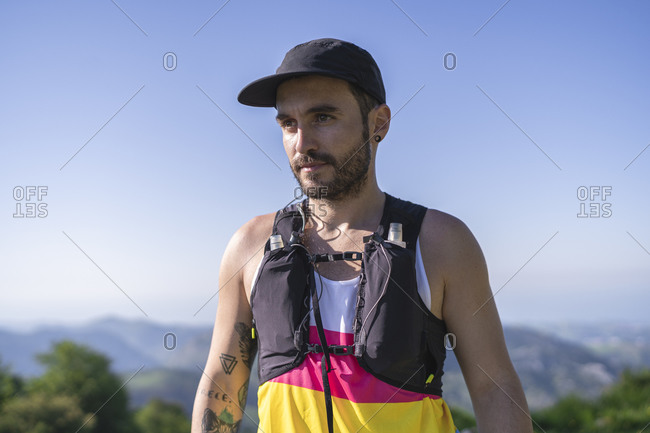 Confident athlete wearing bottle strap admiring view while standing on mountain against clear sky