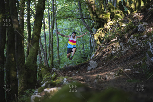 Trail runner running on mountain trail at forest