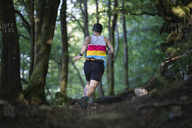 Trail runner running on path of mountain at forest
