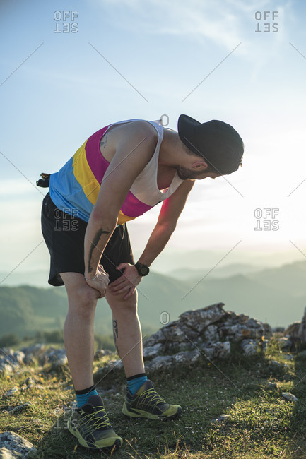 Tired athlete with hand on knee looking at view while standing on mountain