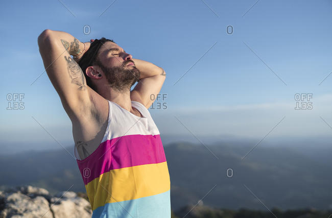 Carefree with hands behind head and eyes closed standing on mountain