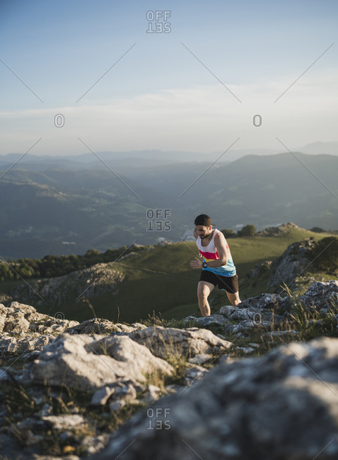 Man running on mountain trail against mountain range and clear sky
