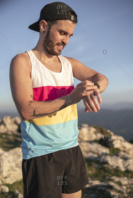 Athlete checking time while standing on mountain against clear sky