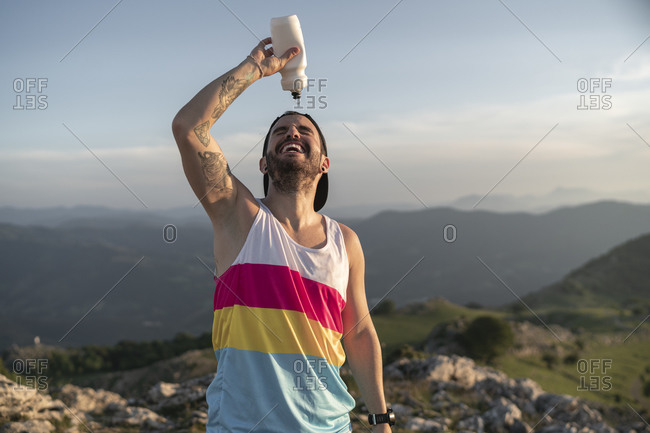Athlete pouring water on face while standing on mountain against clear sky
