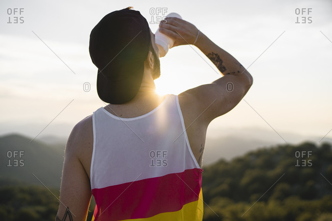 Man drinking water while standing on mountain against clear sky