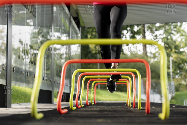 Athlete running over small hurdle by training ground