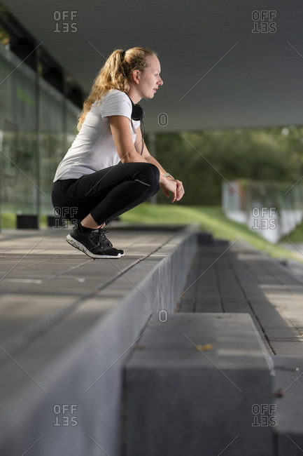 Athlete with headphones around neck crouching at footpath