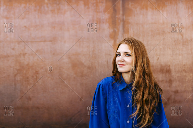 Beautiful redhead woman against brown wall