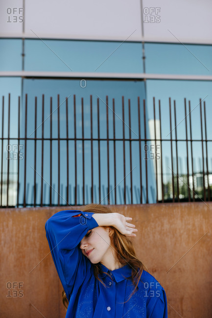 Young woman covering eyes with hand against wall