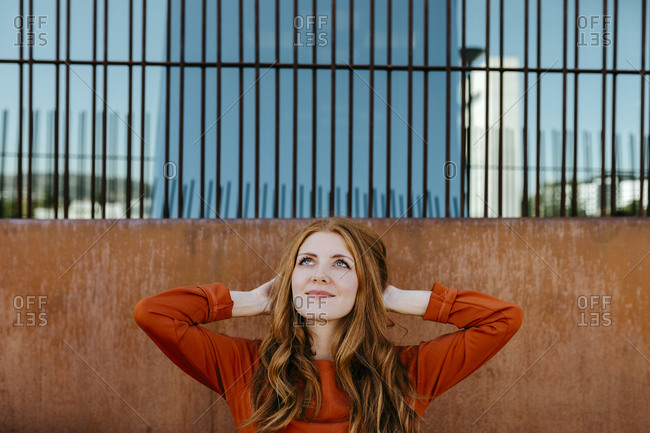 Beautiful young woman with hands in hair looking up while standing against surrounding wall