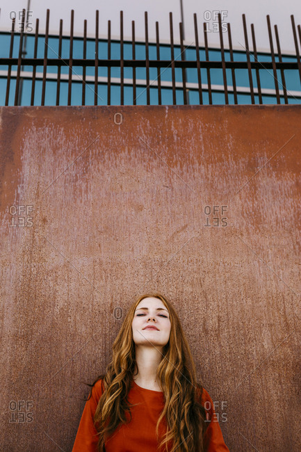 Redheaded beautiful woman leaning against a wall outdoors