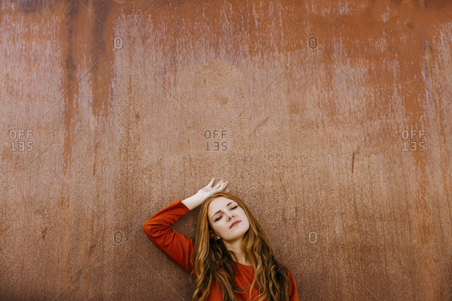 Young woman with eyes closed leaning on brown wall