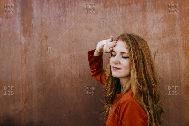 Beautiful woman touching forehead in front of brown wall
