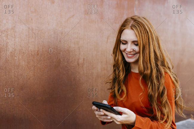 Redhead young woman smiling while text messaging through mobile phone against wall