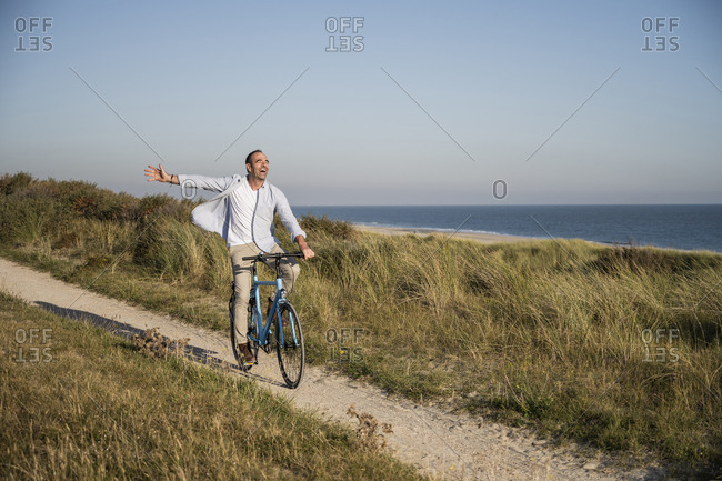 Carefree mature man riding bicycle at beach against clear sky during weekend
