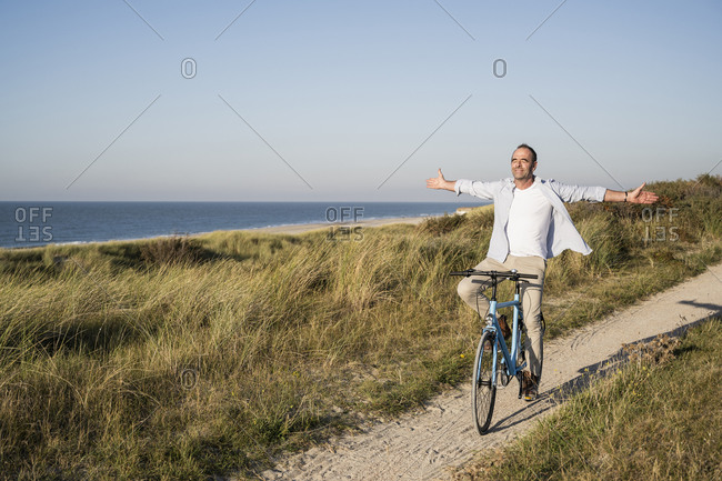 Carefree mature man with arms outstretched closing eyes while riding bicycle at beach