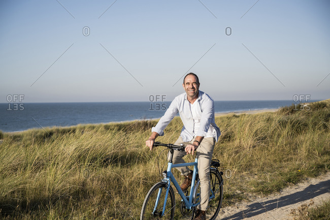 Smiling mature man riding bicycle at beach against clear sky