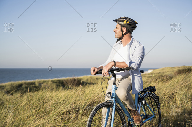 Man looking at view while sitting on bicycle by grassy field against clear sky