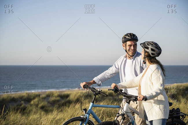 Happy couple in cycling helmets standing with bicycle at beach against clear sky