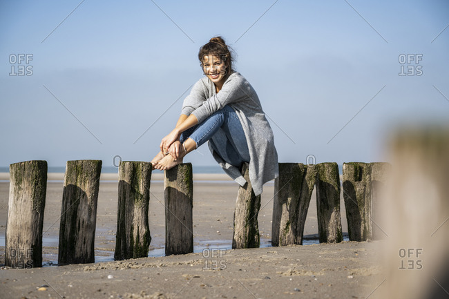 Smiling young woman sitting on wooden posts at beach against sky during sunny day