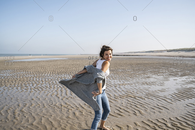 Carefree young woman at beach against clear sky on sunny day