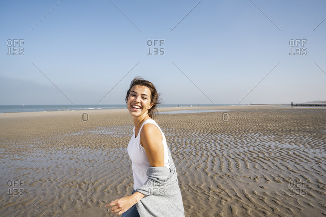 Happy young woman at beach against clear sky during sunny day