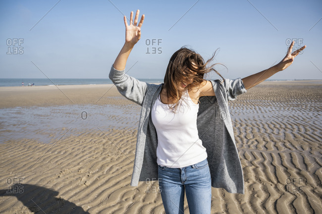 Happy young woman dancing at beach against clear sky during sunny day