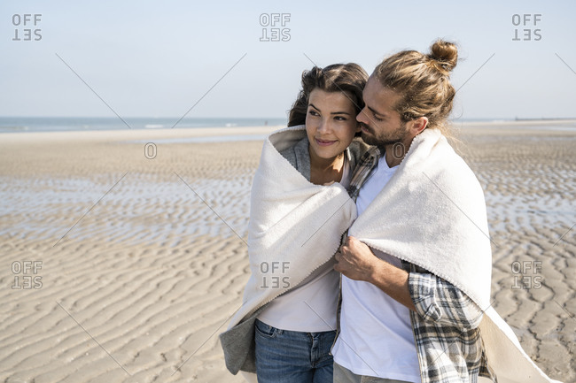 Romantic young couple covered in blanket standing at beach