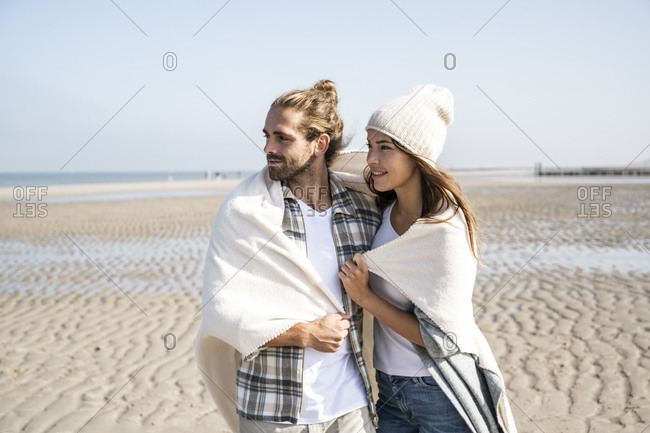 Thoughtful young couple covered in blanket looking away while standing at beach on sunny day