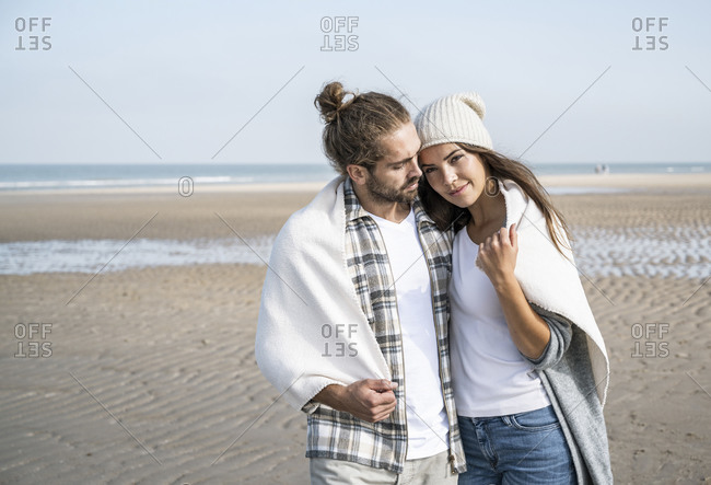 Young couple covered in blanket spending leisure time at beach during weekend