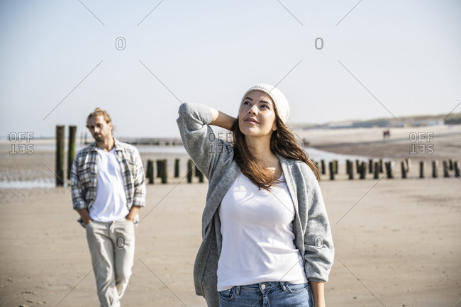 Thoughtful young woman looking up while man walking in background at beach