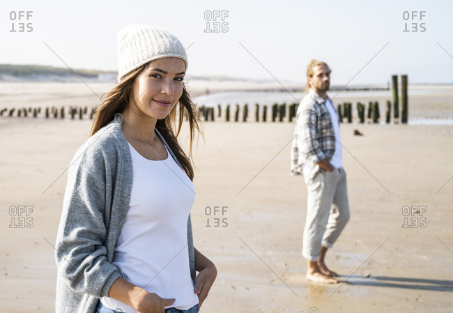Smiling young woman with man at beach during sunny day