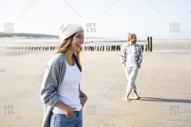 Cheerful young woman standing with hands in pockets at beach during sunny day