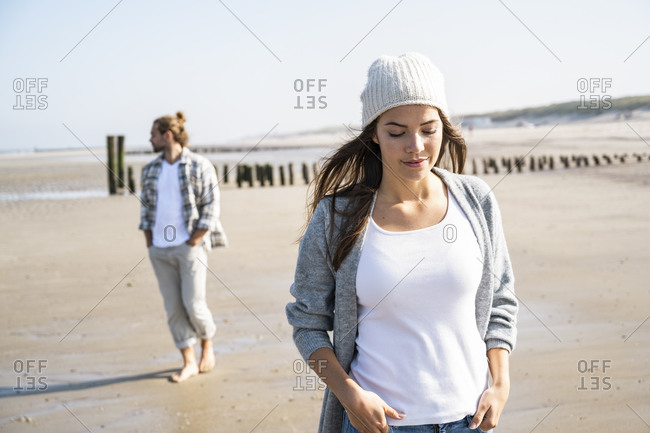 Thoughtful woman with hands in pockets at beach during sunny day