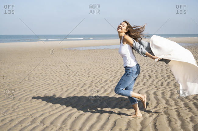 Carefree young woman running while holding blanket at beach during sunny day