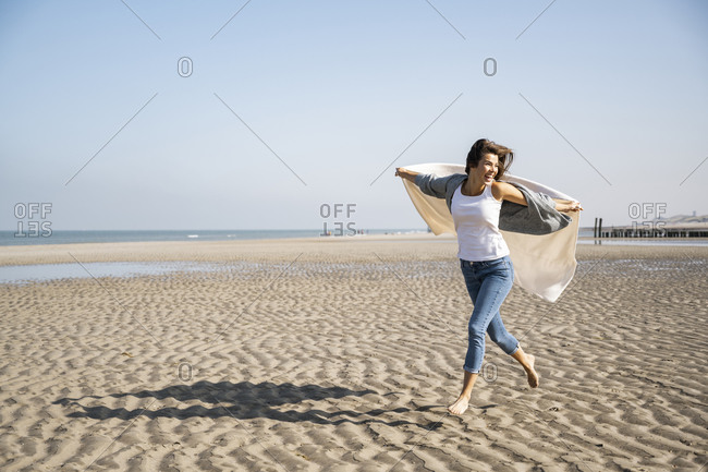 Carefree young woman running while holding blanket at beach against clear sky