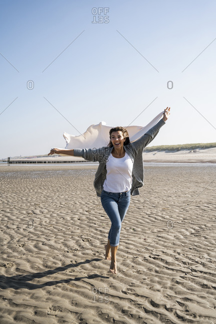 Cheerful woman running while holding blanket at beach during weekend