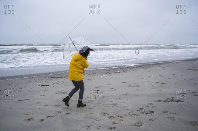Woman in raincoat walking with umbrella at sea shore against sky