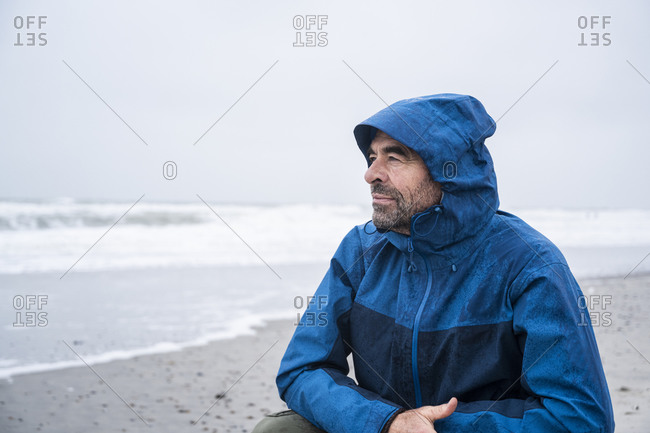 Contemplated mature man in blue raincoat crouching at beach against sky