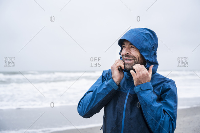 Happy mature man in blue raincoat looking away while standing at beach