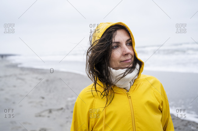 Thoughtful mature woman in yellow raincoat standing at beach against sky