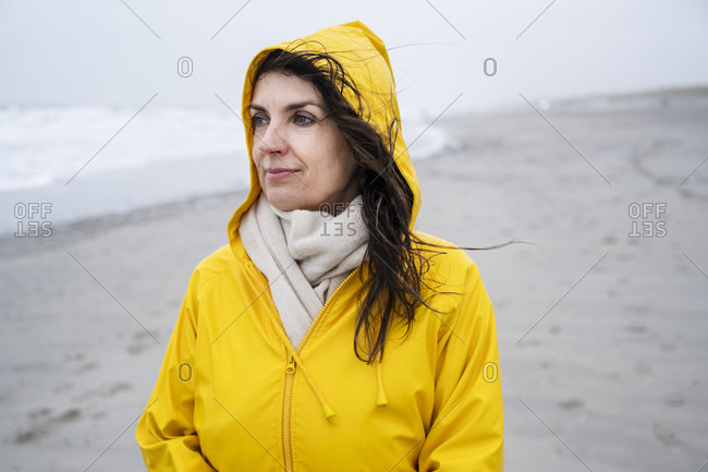Contemplated mature woman in yellow raincoat at beach during weekend