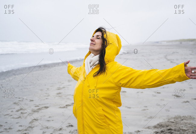 Mature woman in yellow raincoat standing with arms outstretched at beach