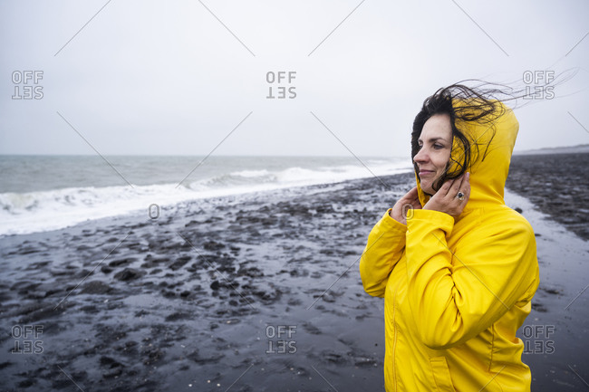 Smiling mature woman in yellow raincoat looking at view while standing on sea shore