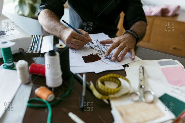 Mature costume designer sketching outfit on paper in studio