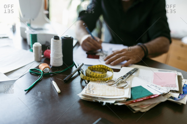 Male costume designer working at table in studio
