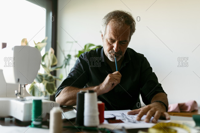 Male costume designer thinking while looking at sketch in studio