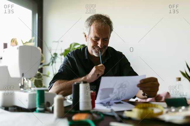 Male costume designer looking at sketch while sitting against wall in studio